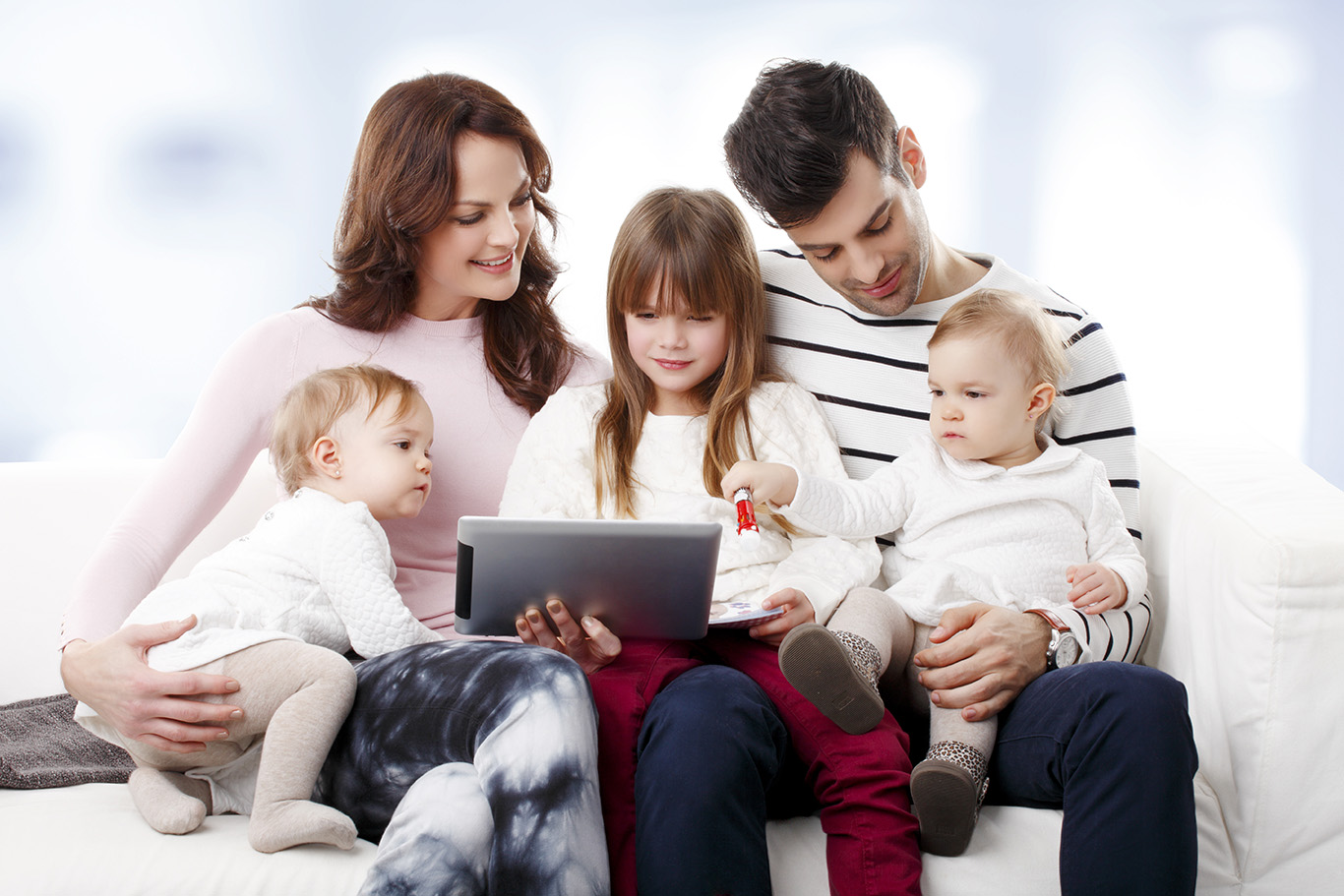 Portrait of happy young family sitting at sofa with twins and preschool daughter while using digital tablet.